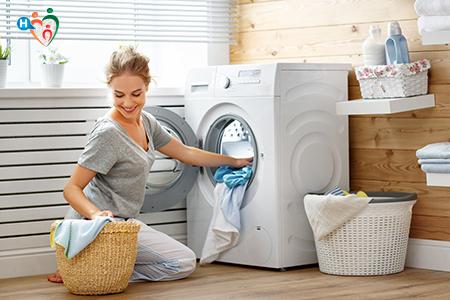 immagine che ritrae una giovane donna nell'atto di fare la lavatrice