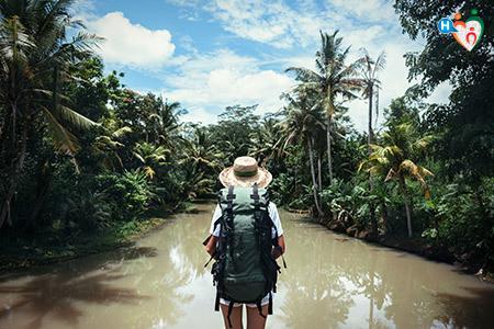 immagine che mostra un ragazzo con lo zaino in spalla che viaggia vicino a un fiume immerso nel verde