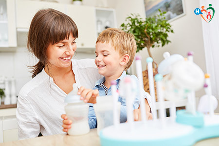 Immagine che mostra una mamma con in braccio un bambino mentre beve il latte