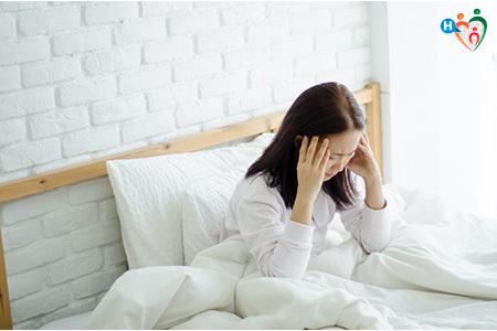 Immagine di una ragazza a letto con il mal di testa