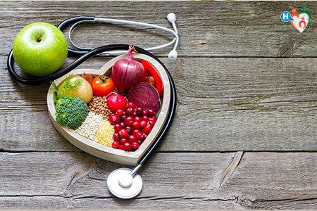 Immagine che mostra alimenti salutari, come frutta e verdura, in un cesto a forma di cuore sopra un tavolo di legno