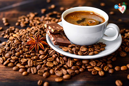 Immagine che raffigura una tazza di caffè circondata da chicchi di caffè