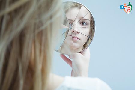 Immagine che mostra una ragazza specchiarsi in uno specchio rotto in più punti