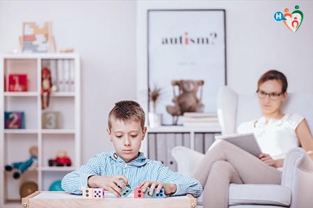 Immagine d un bambino che gioca mettendo in ordine di dadi mentre la mamma lo guarda