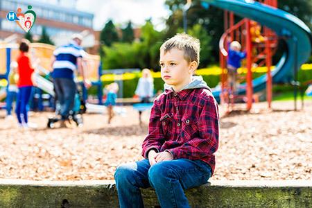 Immagine di un bambino al parco giochi, in disparte che non partecipa con gli altri