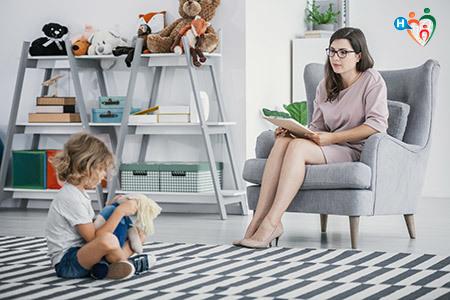 Immagine che mostra una bambina seduta per terra che gioca da sola con una bambola