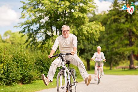 Immagine di due signori in bicicletta nel parco