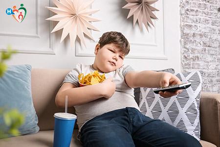 Immagine di un bambino in sovrappeso su un divano mentre mangia cibo spazzatura