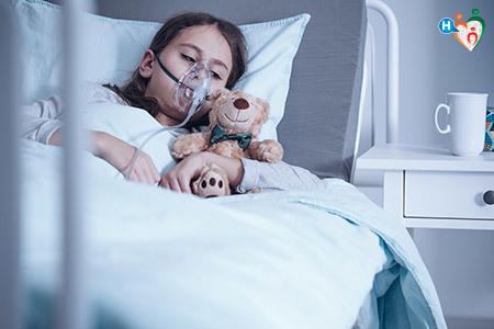 Immagine di una bambina sdraiata in un letto d'ospedale, malata di fibrosi cistica