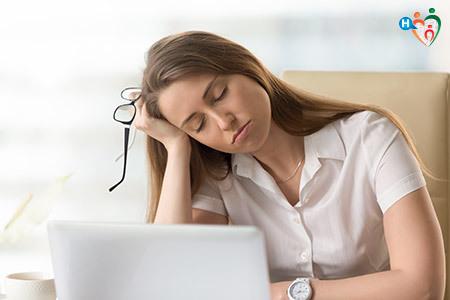 Immagine di una ragazza con la testa appoggiata al braccio e gli occhi chiusi, molto stanca