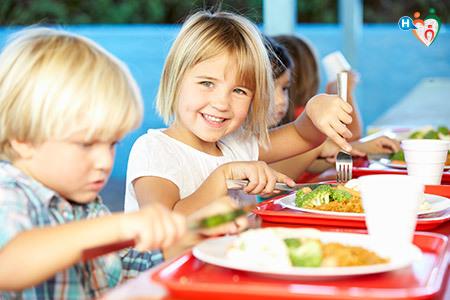 immagine di bambini a tavola mentre mangiano