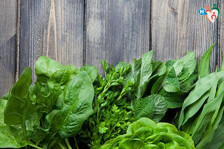 Immagine che mostra delle verdure verdi in foglia su un tavolo di legno