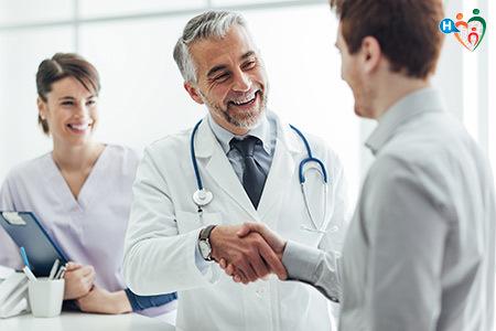 Immagine che mostra un dottore uomo parlare con il paziente, e in secondo piano una dottoressa