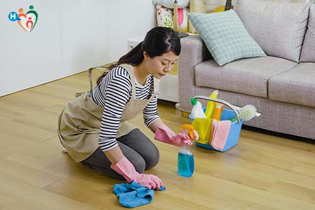 Immagine di una ragazza piegata sulle ginocchia mentre pulisce il pavimento