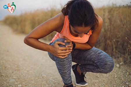 Immagine di una ragazza che, interrotta la corsa, si stringe il ginocchio al petto per il dolore