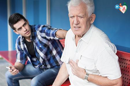 Immagine di un uomo con dolore al petto mentre è in sala d'attesa dell'ospedale insieme a un ragazzo