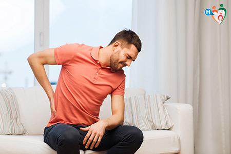 Immagine che mostra un ragazzo seduto sul divano che si tiene la parte bassa della schiena per la lombalgia