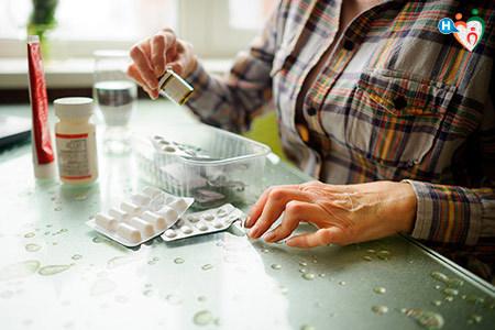 Immagine che mostra una signora affetta da artrite mentre prende le medicine