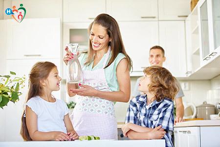 Immagine di una donna che offre dell'acqua ai propri figli