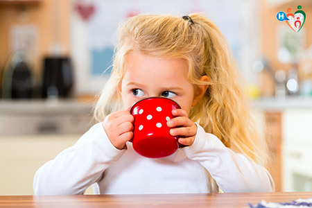 Immagine di una bambina mentre beve da una tazza colorata