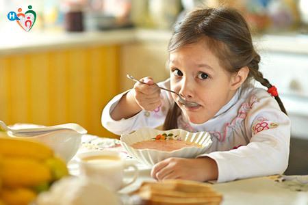 Immagine di una bambina mentre mangia una minestra