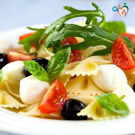 Immagine che mostra un piatto di pasta con pomodori, olive e rucola