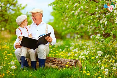 Immagine di un nonno con in braccio un nipotino che leggono al parco