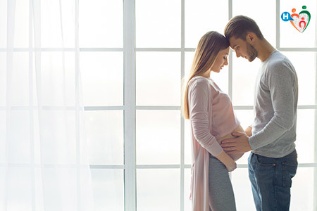 Immagine che mostra una coppia mentre contempla la pancia della moglie incinta