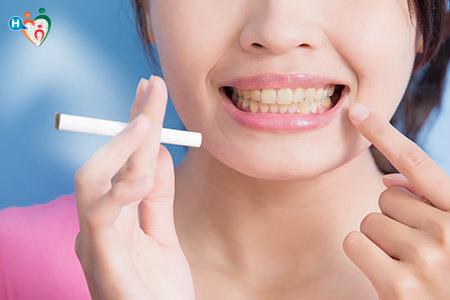 Immagine di una ragazza con in mano una sigaretta che mostra i denti gialli