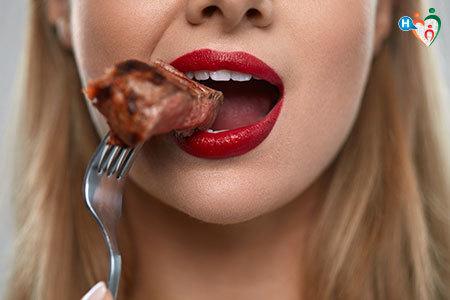 Immagine di una bocca di donna mentre addenta un pezzo di carne