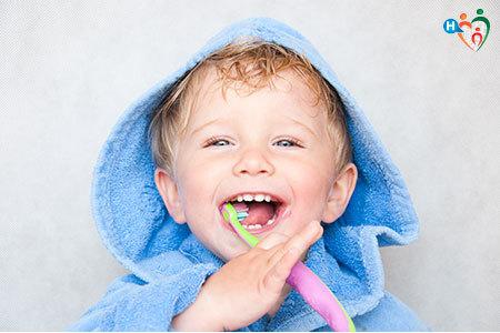 Immagine di un bambino in accappatoio mentre lava i denti