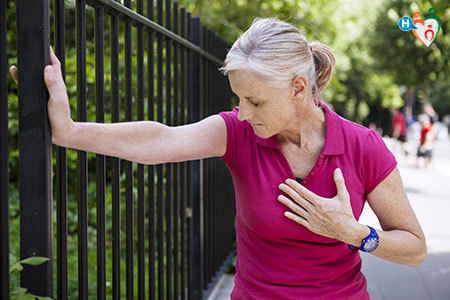 Immagine di una donna che si appoggia a una cancellata perché colta all'improvviso dall'angina pectoris