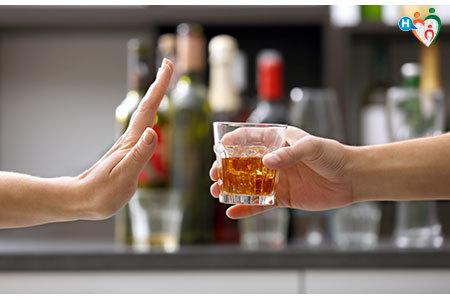 Immagine che mostra una mano rifiutare un bicchiere di liquore
