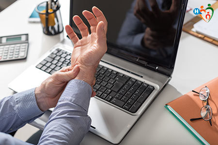 Immagine di un impiegato che si tiene il braccio sofferente per via della sindrome del tunnel carpale
