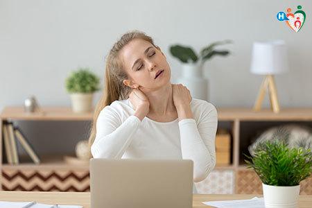 Immagine di una ragazza seduta al pc con male al collo