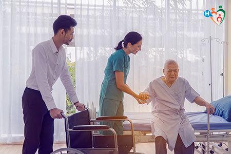 Immagine che mostra due infermieri che aiutano un'anziana