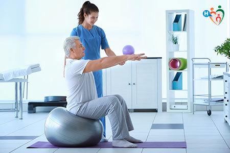 Immagine di un anziano mentre fa dell'esercizio fisico mentre è aiutato da un'infermiera