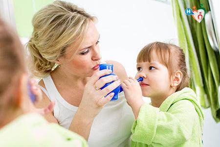 immagine di una mamma che aiuta la sua bambina a fare i lavaggi nasali