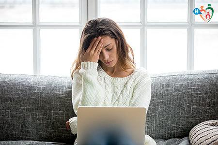 Immagine di una ragazza mentre lavora al computer e si tiene la testa perché sente mal di testa