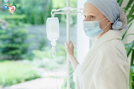 Immagine di una persona malata di cancro con testa e bocca coperte che di appoggia all'asta a cui è attaccata la flebo per guadare fuori dalla finestra