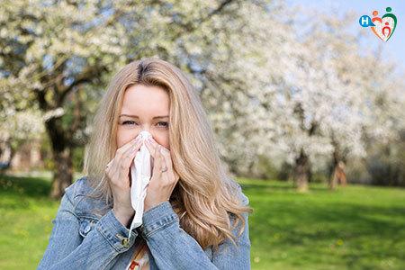 Immagine di una ragazza in un parco con molti alberi che si soffia il naso in preda all'allergia
