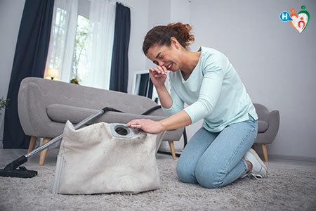 Immagine di una donna mentre starnutisce quando svuota l'aspirapolvere