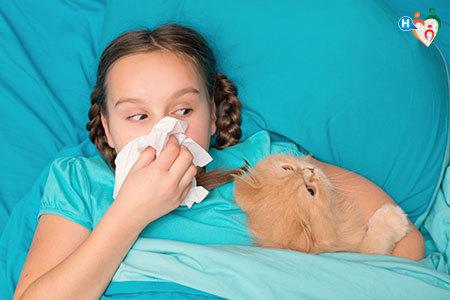 Immagine di una bambina sdraiata a letto con in braccio un gatto mentre si soffia il naso