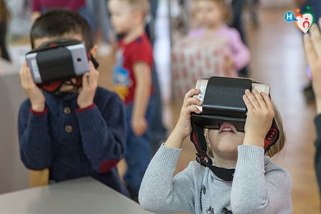 Immagine di due bambini che guardano con un viseo per la realtà aumentata