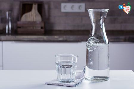 Immagine di una caraffa d'acqua appoggiata su un tavolo di legno accanto a un bicchiere