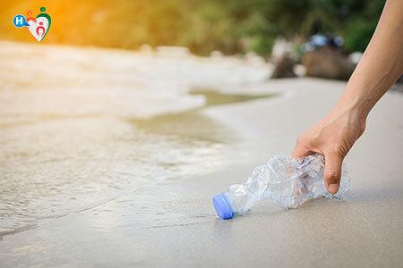 Immagine di una ano che raccoglie una bottiglia di plastica da una spiaggia