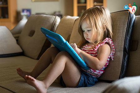 Immagine di una bambina seduta su un divano mentre gioca con un tablet