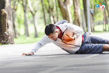Immagine di un uomo accasciato a terra in un parco in preda a un infarto