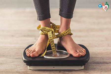 Immagine di un ragazzo che si sta pesando su una bilancia con i piedi annodati da un metro per sarti