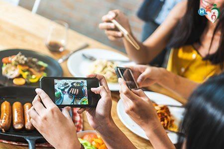 Giovani donne fotografano del cibo su un tavolo